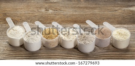 a row of measuring scoops of gluten free flours - almond, coconut, teff, flaxseed meal, whole rice, brown rice, buckwheat