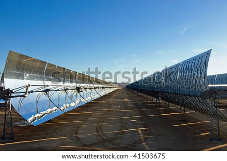 A row of mirrors at a solar energy station in the desert. - stock photo