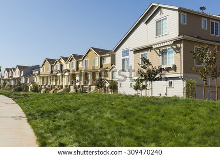 A row of new apartments with a lush grassy lawn in the foreground - stock photo