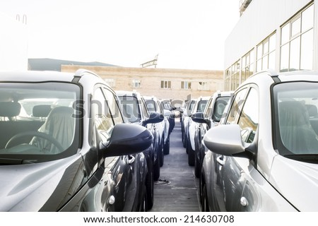 A row of new cars parked at a car dealer shop - stock photo