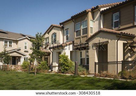 A row of new townhomes with a lush grassy lawn in the foreground. - stock photo
