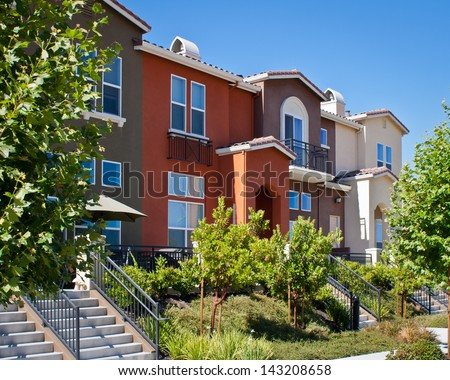 A row of new townhomes with yellow, gray, and dark red exteriors in San Jose, California. - stock photo