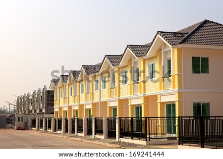 A row of new townhouses in construction site - stock photo