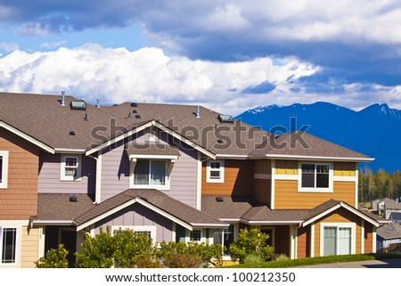 A row of new townhouses or condominiums with blue sky and clouds - stock photo