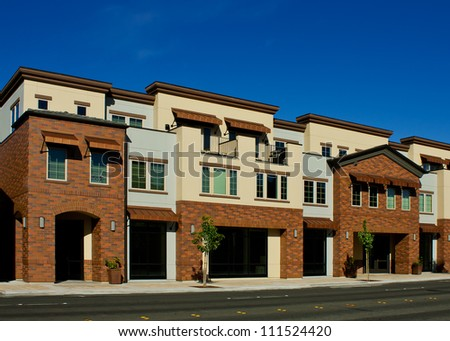 A row of newly-constructed apartments with shop storefronts below. - stock photo
