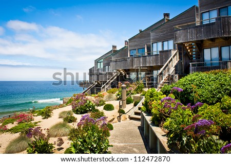 A row of oceanfront townhomes adjacent to a landscaped sand dune along the California coast. - stock photo