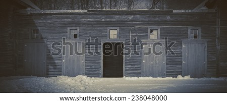 A row of old barn doors, with one open under the moonlight. - stock photo