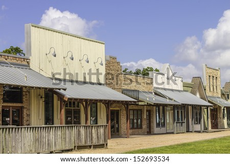A row of old western rural shops with a bright blue sky in the background. - stock photo