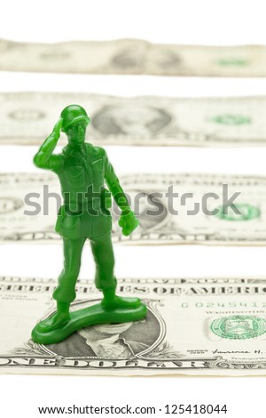 A row of one dollar bills with military toy - stock photo