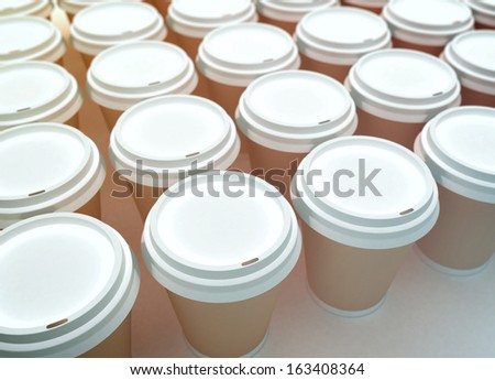 A row of paper coffee cups on a white background. - stock photo