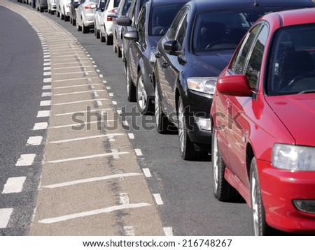 A row of parked cars curving around bend in road