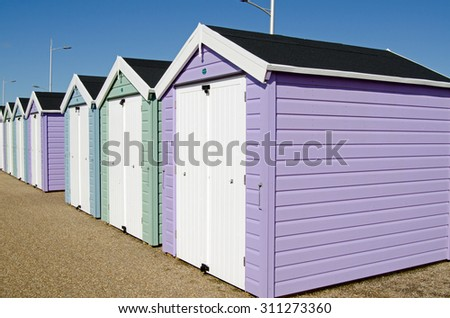 A row of pastel coloured beach huts overlooking the sands at Weston-Super-Mare.  Viewed from pavement on a sunny day in August.
