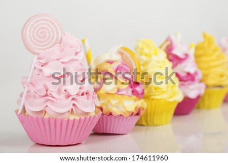 a row of pink and yellow cupcakes on a white background - stock photo