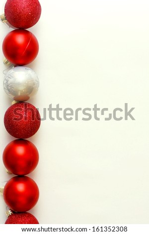 a row of red and silver sparkly christmas ornaments are lined up vertically on a white background - stock photo