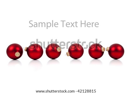 A row of red Christmas ornaments/baubles on a white background with copy space - stock photo