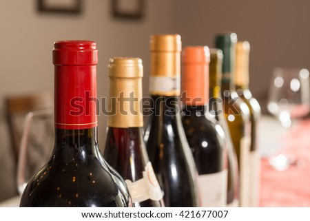 A row of sealed and unlabeled wine bottles with glass in the background.
