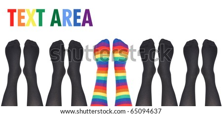 A row of socks are lined up on a white isolated background but the middle feet are rainbow colored and original. Use it for a creative or unique concept.