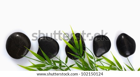 A row of spa massage stones and bamboo leaves on a white background with copyspace - stock photo