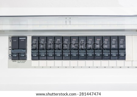 A row of switched off household electrical circuit breakers on a wall panel
