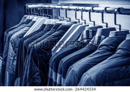 A row of t-shirts hanging on hangers - stock photo