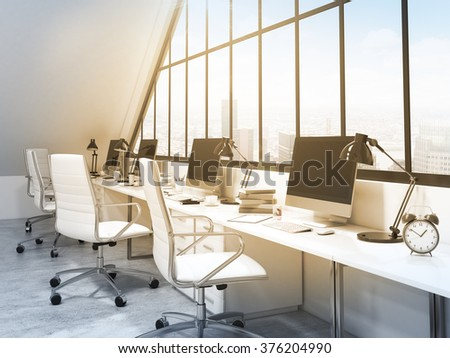 A row of tables in front of the panoramic window in an office in an attic. Computers and stuff on them. City view. Filter, Toned image. Concept of a modern office. 3D rendering - stock photo