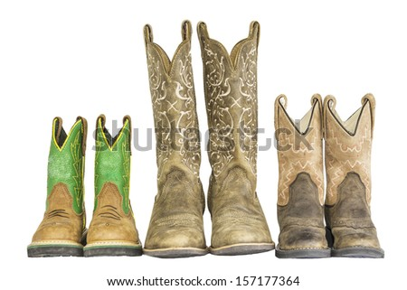 A row of three pairs of cowboy western boots isolated on a white background. - stock photo