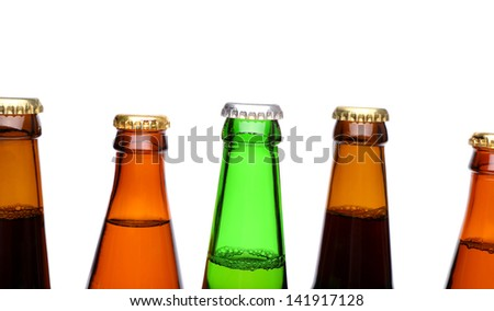 A row of top beer bottlenecks on a white background with a reflection.