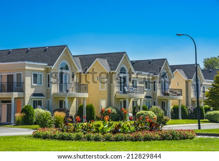 A row of townhouses on street with road and flower land in front. Townhouses on sunny day in British Columbia - stock photo
