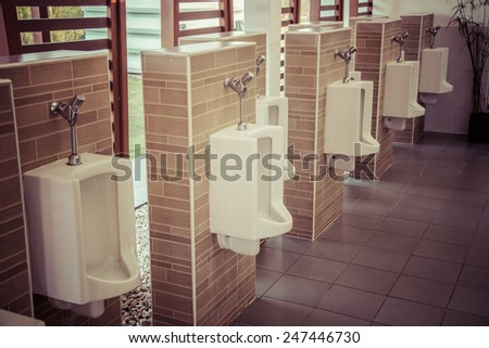 A row of urinals in tiled wall in a public restroom focusing, process color - stock photo