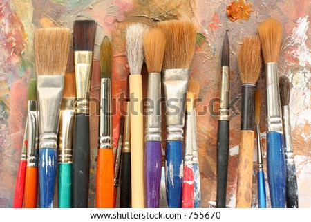 a row of well-used brushes against a paint palette background - stock photo
