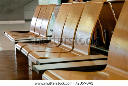 A row of wood chairs in the airport - stock photo
