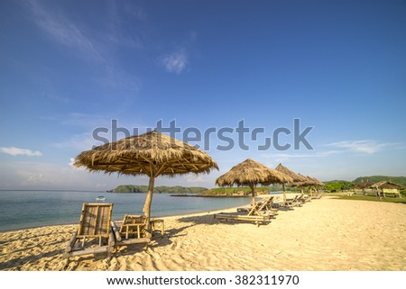 A row of wooden lounge with direct sunlight at Lombok beach, Indonesia - stock photo