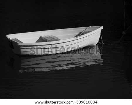 A rowboat in black and white moored in harbor. - stock photo