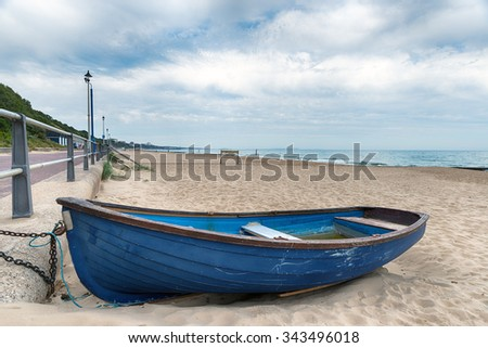 A rowing boat on the beach at Bournemouth on the Dorset coast - stock photo