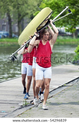 A rowing team carrying their boat to the boat house after a race - stock photo