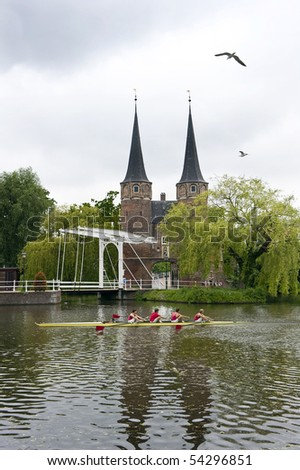 A rowing team in a coxed four rowing past a historic, fortified, city gate in Delft, the Netherlands - stock photo