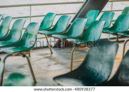 A rows of plastic fiber glass seats chairs on the platform stadium ferry bus. Shallow focus. Vintage effect.