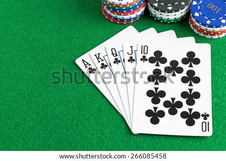 A royal flush poker hand with chips and green felt table copy space for your text - stock photo