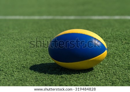 A rugby ball on a synthetic grass in front of the white line. - stock photo