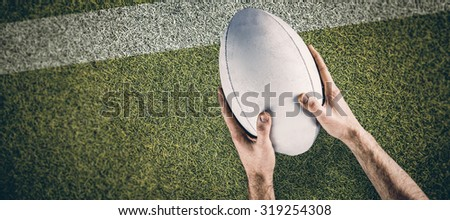 A rugby player posing a rugby ball against pitch with line - stock photo