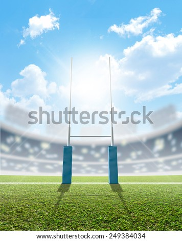 A rugby stadium with rugby posts on a marked green grass pitch in the daytime under a blue sky - stock photo