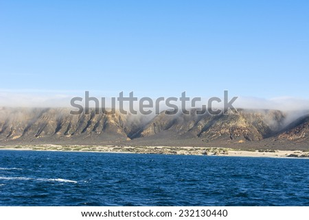 A rugged, uninhabited island with deep canyons framed against a blue sky and deep, turquoise water during sunrise - stock photo