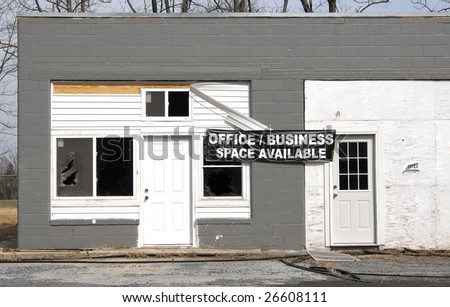 A run down, unkempt concrete building advertises office space for rent. - stock photo