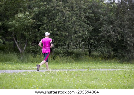 A runner jogging in the summer. Weather is a bit dull and it is raining.