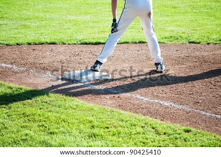 A runner waits on first base for the next hit - stock photo