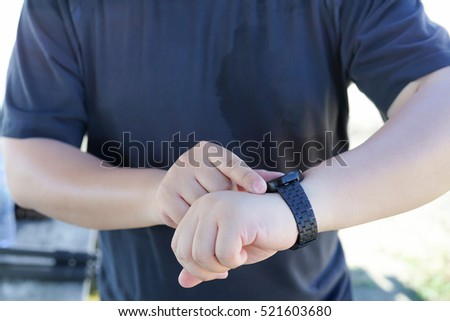 a running man checking / looking heart rate on smart watch after running course, Technology smartwatch background concept