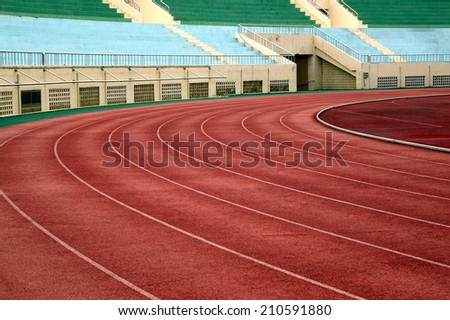 A running track in a stadium with markings in white and red. - stock photo