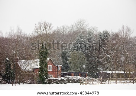 A rural home in England during heavy snowfall. - stock photo