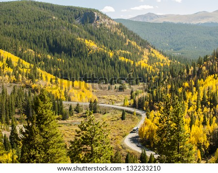 "A rural mountain road with a winding ""S"" curve. Autumn landscape in Colorado."