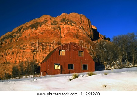 A rural red barn in Colorado winter snow showcasing the state's blue skies